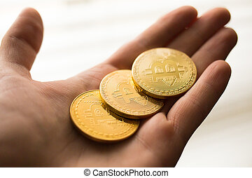 Three bitcoin coins in a hand close up