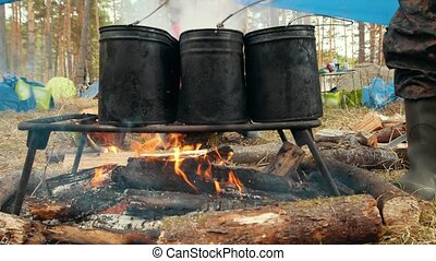 Three black iron cauldrons on the bonfire for cooking food,...