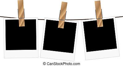Three blank polaroid frames hanging on a rope