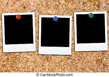 Three blank polaroids affixed on cork board with colorful...