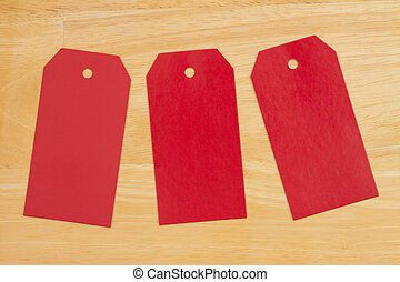 Three blank red gift tags on wood