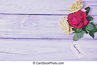 Three blossoming roses on a white wooden background