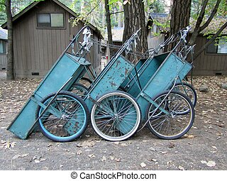 Three blue camping gear carts near cabins