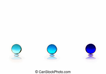 Three blue marbles, ranging from light to dark blue, on a white background