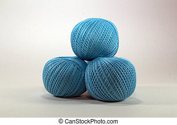 three blue skeins of natural cotton for needlework on white background