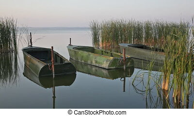 Three boats are reflected in quiet water at sunrise
