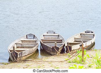 Three boats on coast of the river