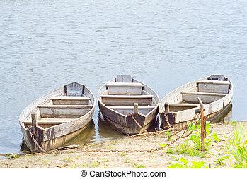 Three boats on coast of the river