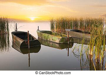 Three boats on the lake at sunrise