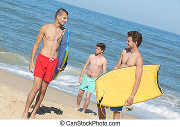 three bodyboard surfers at the beach