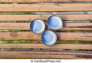 three bottle cap on bamboo