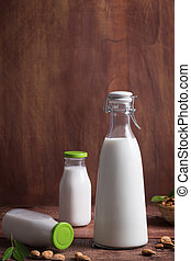 Three bottles of almond milk on a brown wooden table