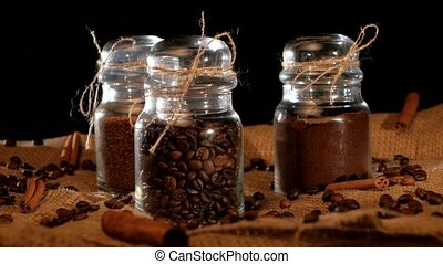 Three bottles of different coffee inside on black background...