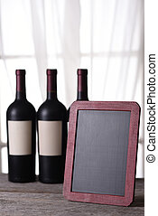 Three bottles of red wine and blank chalk board