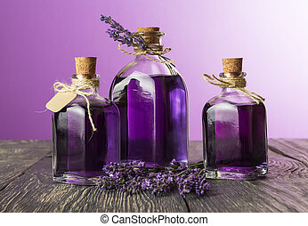 Three bottles with a fragrant tincture of lavender and fresh twigs on purple background