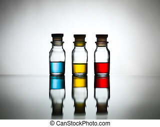 Three bottles with colored solution on table