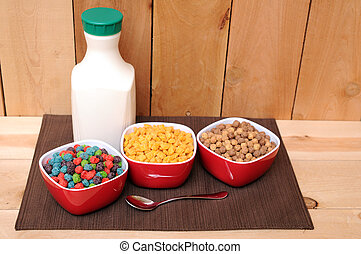 three bowls of cereal and milk bottle