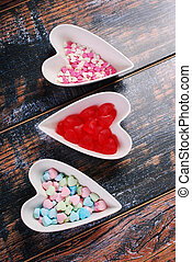 Three bowls with heart shaped candies on shabby background