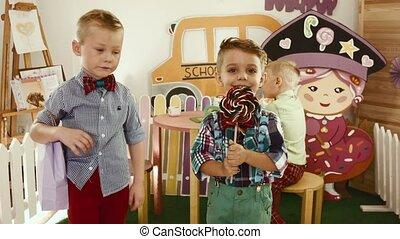 Three boys dance with big candies