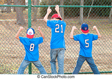 Three brothers next to fence at a baseball park.