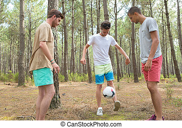 three boys playing football in the forest