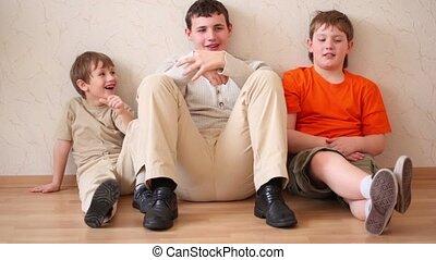 Three boys sit, looks forth and talk - Three boys sit...