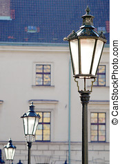 Three brass antique street lamps in a row