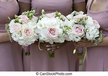 three bridesmaids holding wedding bouquet