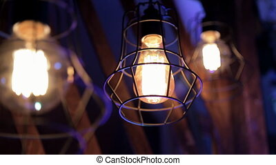 Three bright lanterns in metal grilles burn in the blue...