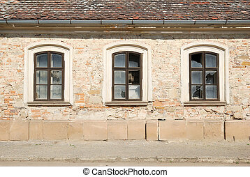 Three broken windows in a wall of a damaged house