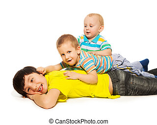 Three brothers laying on each other and having fun