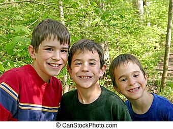 Three Brothers Playing Outside in the Woods