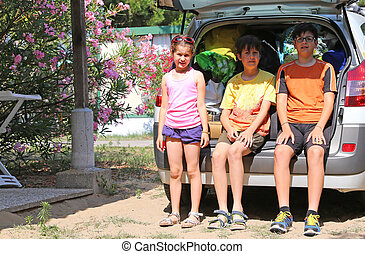 three brothers sitting in the trunk of the car during the summer holidays