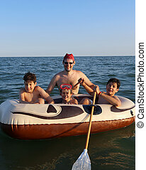 three brothers with their father on the dinghy in the sea