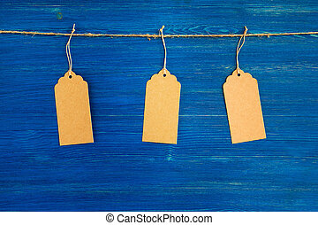 Three brown blank paper price tags or labels set hanging on a rope on the blue wooden background.