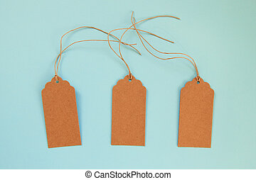 Three brown blank paper price tags or labels set on the blue background, top view.