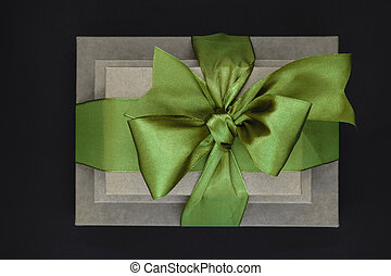 Three brown carton gift boxes bundled with green ribbon isolated on black background and view from above