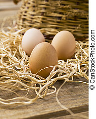 three brown eggs on a wooden table
