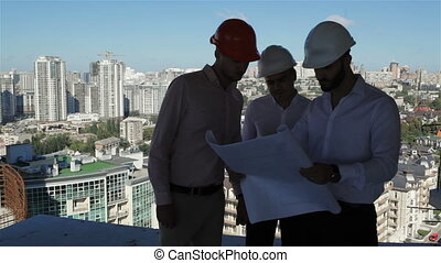 Three builders examine the project of building under construction