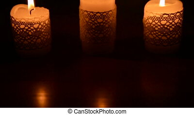 Three burning candles in the dark