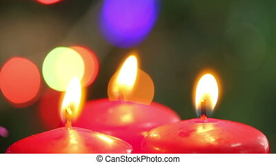 three burning candles on a background garlands blinking