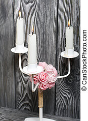 Three burning candles on a background of brushed boards.