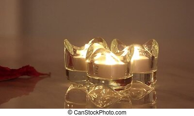 Three burning e-candle in a crystal candle holder.
