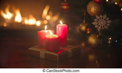 Three burning red Christmas candles on dinner table at living room next to fireplace and Christmas tree