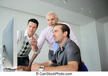 Three business colleagues gathered around computer
