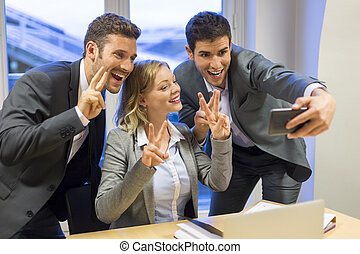 Three business peolpe do a happy Selfie in the office