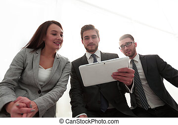 three business people are looking at a tablet PC