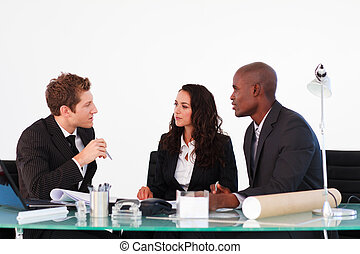 Three business people discussing in a meeting