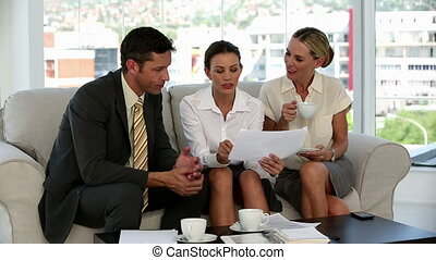 Three business people on a sofa looking at a document and pointing at it