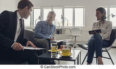 Three business people sitting around a coffee table
